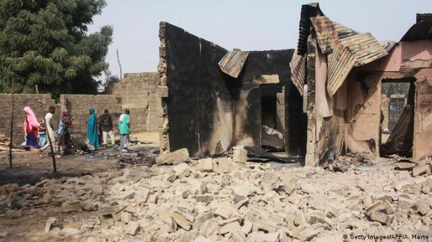 The rubbled remains of a house in Maiduguri, Nigeria, after a Boko Haram attack. A small group of children are standing to the left side.