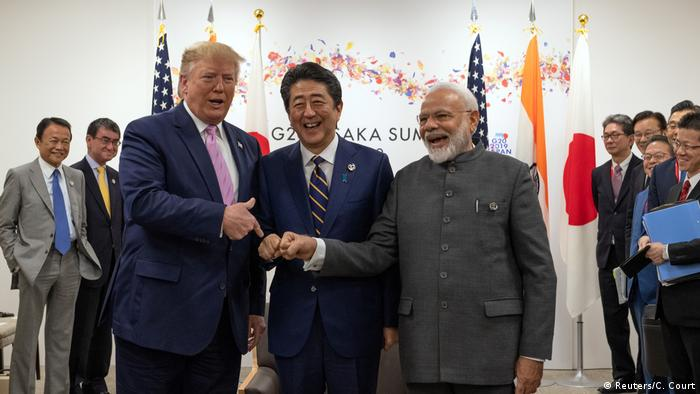 U.S President Donald Trump jokes to the media about fist bumping with Japan's Prime Minister Shinzo Abe and India's Prime Minister Narendra Modi (Reuters/C. Court)