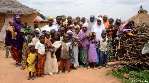 Men, women and children pose for a picture in the village (DW/K. Gänsler)