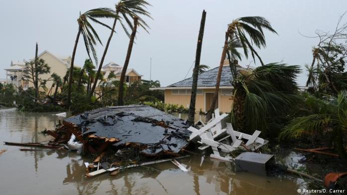 The hurricane overturned cars and tore roofs after making landfall in the Bahamas. Many islanders have been evacuated.