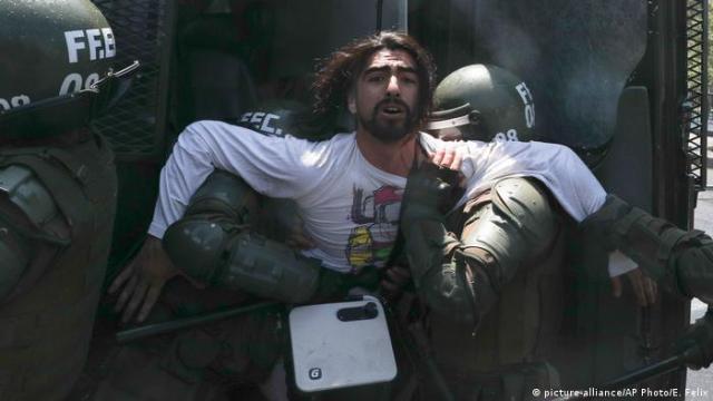 Forças de segurança detêm manifestante durante protesto em Santiago