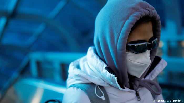 China Frau mit Schutzmaske im Bahnhof von Peking