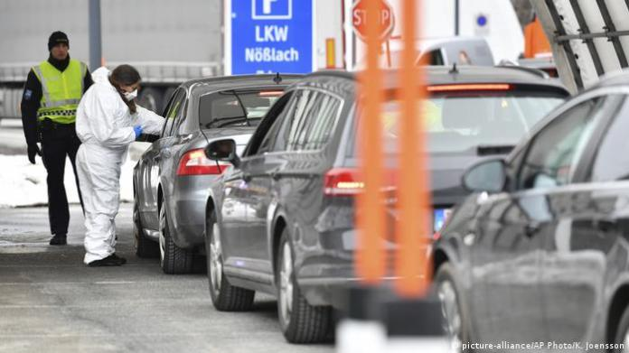 A medical professional on the Austrian-Italian border measures the temperature of a car driver from Italy.
