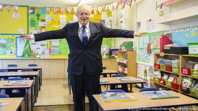 British Prime Minister Boris Johnson stretches his arms out in a school classroom.