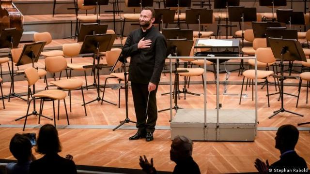 Kirill Petrenko alone onstage, hand on heart in a gesture of gratitude to applauding concert visitors (Stephan Rabold)