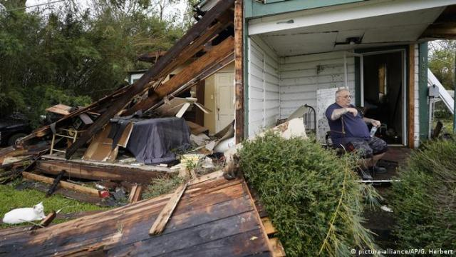 A man sits outside his damaged house in Lake Charles