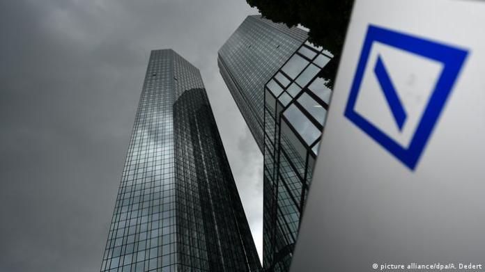 Deutsche Bank's skyscraper headquarters in Frankfurt, Germany under a dark grey sky