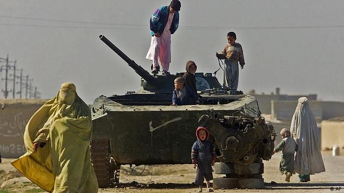 Afghan chidren play atop an abandoned Soviet-made armored vehicle, which was left after the 1979-89 Soviet occupation, while women pass by in the village of Elmarab, near Mazar-e-Sharif, Monday, Feb. 11, 2002.