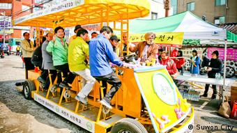 Festival organizers join Mayor Yeom on a bicycle-bus tour of the neighborhood