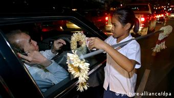Thai school girl Wipa Hunthond, 11 years old, works at her job selling flowers to motorists on busy Asok intersection in Bangkok, Thailand, Wednesday 16 November 2005, still dressed in her school uniform. Her working day starts after school at 1600 and normally finishes at around 2300, or until she has sold out all her daily garlands. Wipa who goes to the Sawasdee School, is one of seven children who work this polluted intersection to help her family meet costs. Hundreds of school children in Bangkok and other Thai cities work daily like Wipa before and after school to make ends meet. As Asia celebrates the United Nations Universal Children's Day set this Sunday 20 November 2005, the world's fastest growing region faces increasing demands to protect the rights of children and provide for them their daily needs. Foto: Narong Sangnak +++(c) dpa - Report+++