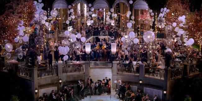 A lavish 1920's mansion is filled with party-goers dancing and drinking in revelry. The two-story mansion is decorated throughout, and the center stairway is glistening with golden lights, tinsel, and the buzz of decadence in the air.]