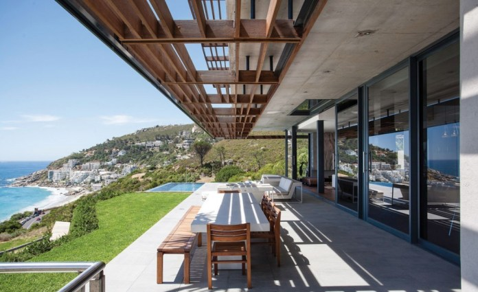 Modern outdoor dining area with white long dining table and wood chairs