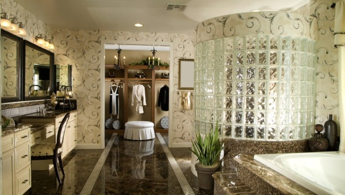 Large luxury bathroom with glass tile shower, marble-enclosed tub and access to walk