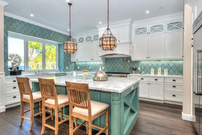 Traditional l-shaped kitchen with white cabinets & marble countertops along with cement tile backsplash