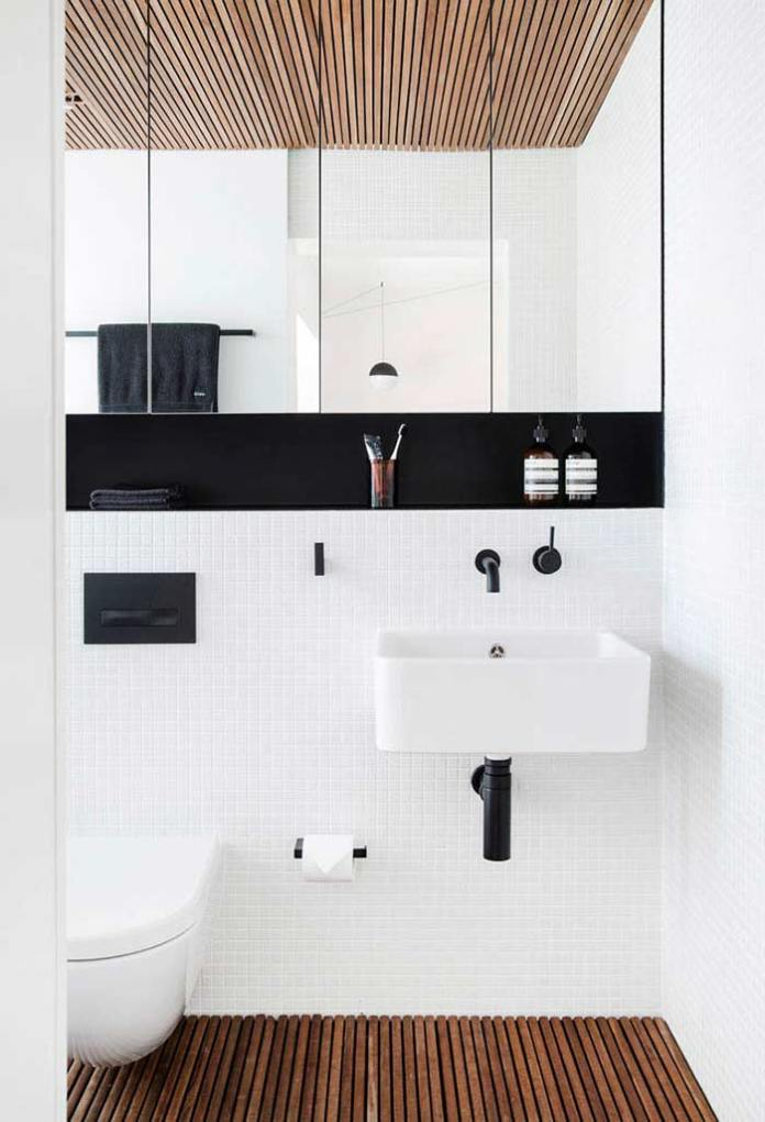 A black and white bathroom that follows the trends white tiles, wood on the ceiling and floor, as well as brushed black china