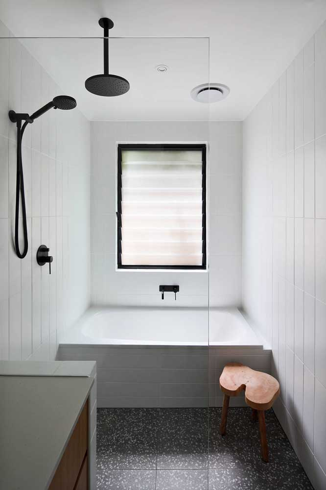 A charming wooden stool to complement the look of the small bathroom with a bathtub.