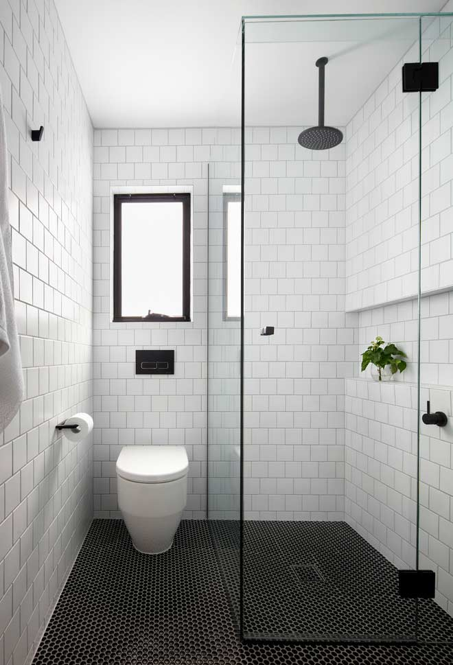 black and white bathroom with rectangular tiles and a ceiling shower to give it a more industrial touch