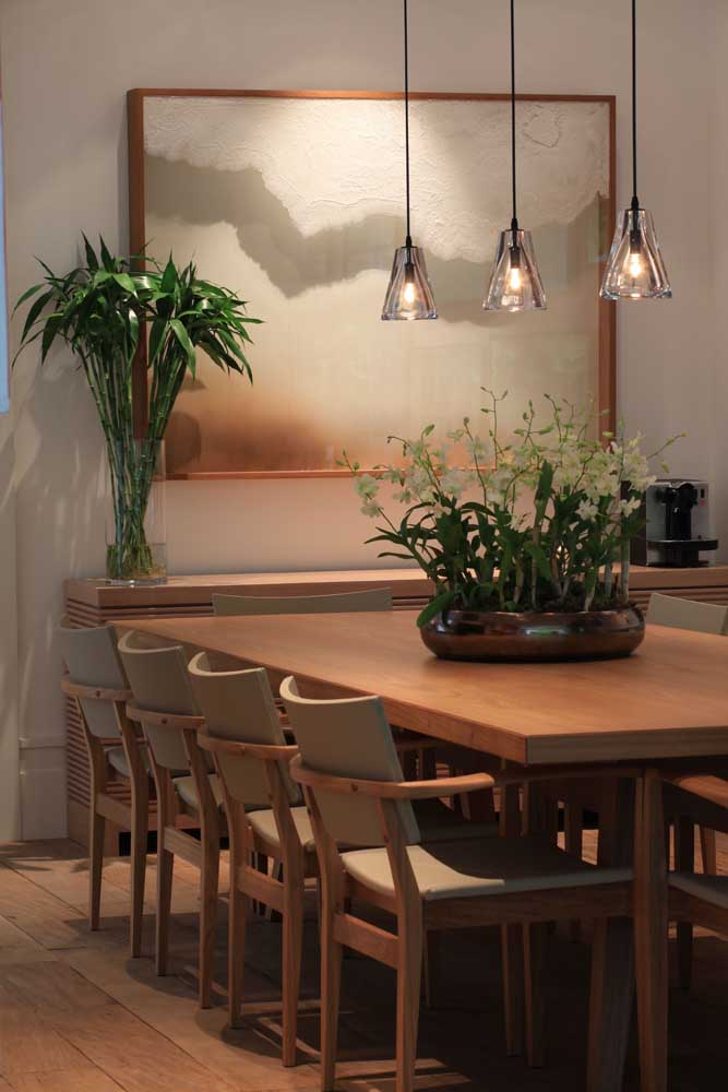 35. The trio of pendant lamps enhances the arrangement of orchids on the dining table.