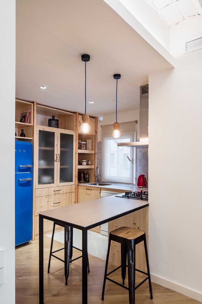 45. Small kitchen with wooden furniture and industrial pendants to highlight the modern concept.