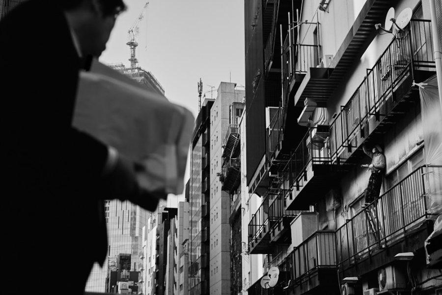 A man repaints a building in Tokyo