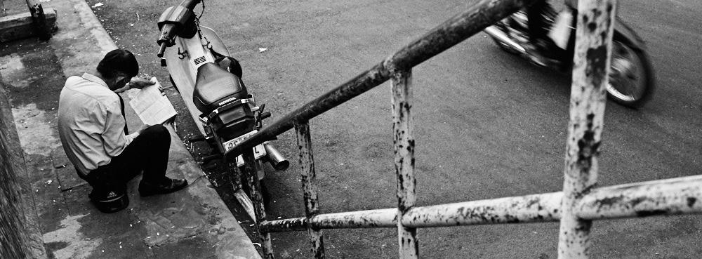 Hanoi, Vietnam - Reading the paper on an Adidas helmet
