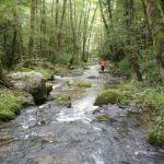 Loïc arpente la rivière Selves avec un sac à dos étanche