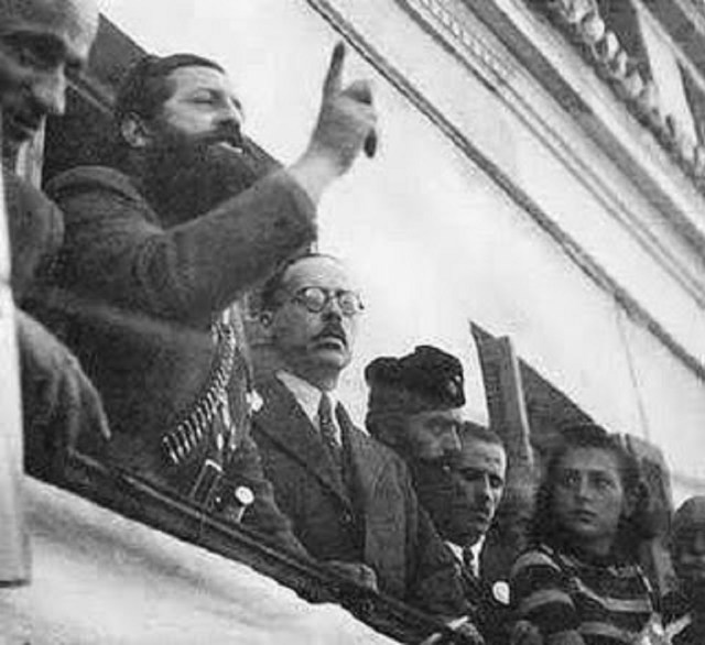 Ο μπαμπάς του Σημίτη εκ δεξιών του Άρη Βελουχιώτη την ώρα που αυτός έβγαζε το γνωστό του λόγο στη Λαμία. Από τραπεζίτης αρχικομμουνιστής! Ο Άρης αποκεφαλίστηκε, ο Γεώργιος μεγαλούργησε οικονομικά και ο υιός του διέλυσε τη χώρα