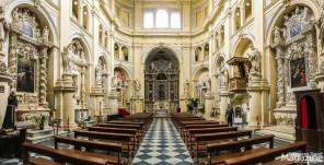 The interior has a unique elliptical plan, with side walls punctuated by short chapels with altars