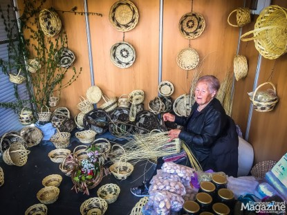 This elderly lady adroitly bends reeds into baskets,