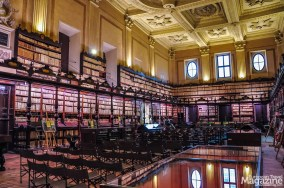 The library has a coffered ceiling and dark wooden shelves, intricately carved and beautifully lit