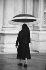 A nun run away from the rain in a busy afternoon