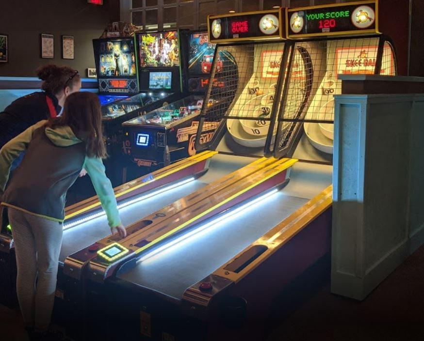 Pinball and Skee-ball in game room at bar