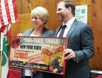 "Retiring CCE-MC team member Debbie SeGuin was honored for her more than 30 years of service to the organization and given a vintage New York farmers market sign as a gift during the CCE-MC annual meeting on Dec. 4. ""Debbie is the rock that really holds these sort of organizations together,"" CCE-MC President Cory Mosher said. Pictured: SeGuin and Mosher pose with the vintage sign. (photo by Jason Emerson)"