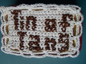 Crocheted and cross stitched cover of the Tin of Tans