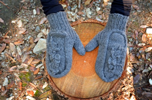 Holly mittens seen from above, resting on a stump