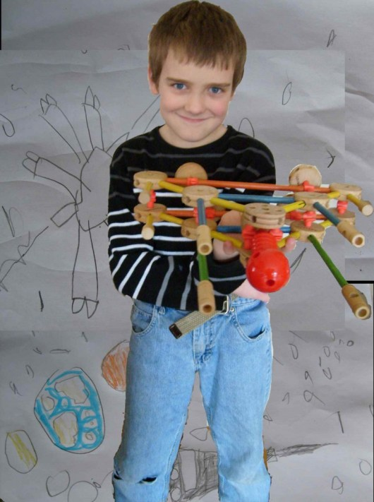 M holding a tinkertoy rocket ship with a background of his space drawings