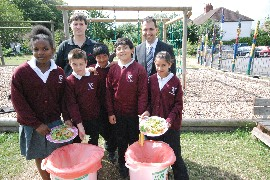 Councillor Bassam Mahfouz recycling food waste with pupils from Wood End Junior School