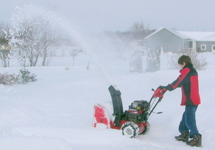 boy blowing snow in driveway