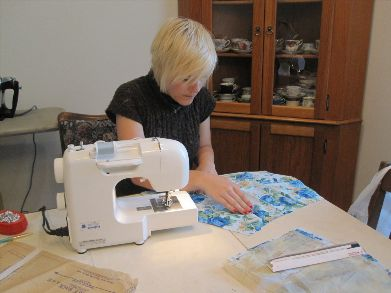 person sewing with sewing machine