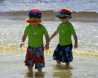 identically dressed twins playing in shallow ocean water