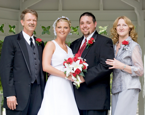 bride and groom standing at altar with parents