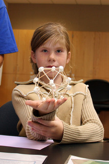 girl holding toothpick and marshmallow model of a cell