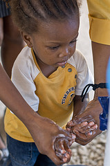 adult helping child wash her hands