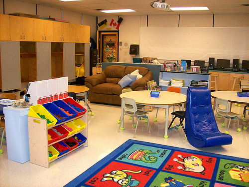 elementary classroom with tables, carpet, books, cubbies