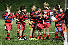 young boys in football uniform discussing ball