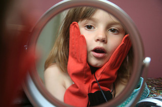 young girl with fancy gloves looking in round mirror