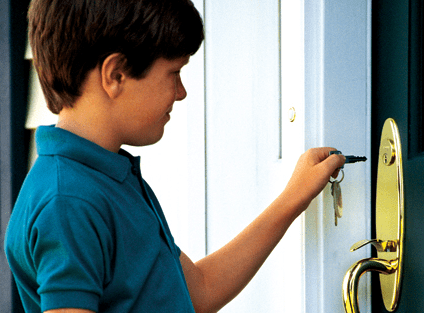 young boy opening door with key