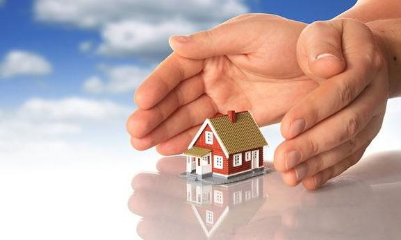 pair of hands over model of a home
