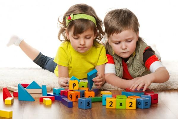 boy and girl on floor playing with blocks