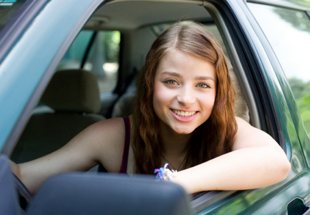 teen girl smiling from front of car